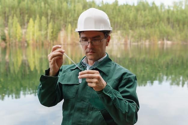 Ekolog przemysłowy lub chemik pobiera próbkę wody z jeziora na terenie zalanego kamieniołomu