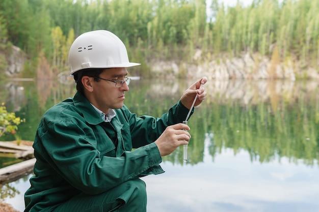 Ekolog przemysłowy lub chemik pobiera próbkę wody z zalanego kamieniołomu