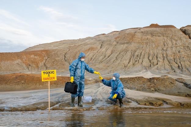 Ekolog w odzieży ochronnej pobierający próbkę zanieczyszczonej wody lub gleby z ręki kolegi podczas badań naukowych w niebezpiecznym obszarze