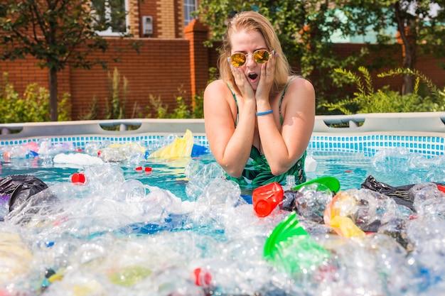 Ekologia, plastikowe śmieci, zagrożenie środowiska i zanieczyszczenie wody - zszokowana kobieta na brudnym basenie.