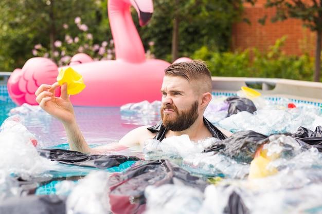 Ekologia, plastikowe śmieci, zagrożenie środowiska i zanieczyszczenie wody - zszokowany mężczyzna pływa w brudnym basenie.
