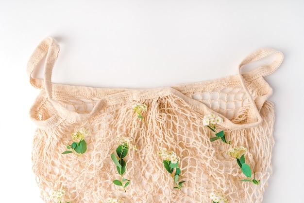 Ekologiczna bawełniana ekologiczna torba wielokrotnego użytku z wiosennymi kwiatami widok z góry piękna minimalistyczna kompozycja kwiatowa