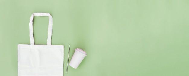 Ekologiczna biała torba papierowa, metalowa słomka do napojów, filiżanka kawy na zielonym tle płaskie leżące, kopia przestrzeń