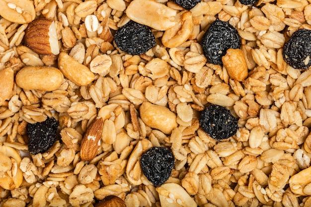 Ekologiczna domowa pieczona granola z orzechami i rodzynkami na blasze do pieczenia. jedzenie na śniadanie. posiłek tło, musli tekstury. widok z góry. fotografia makro.