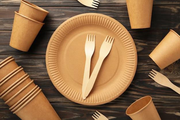 Ekologiczna jednorazowa zastawa stołowa na brązowym tle. widok z góry