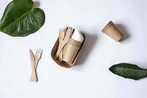 Ekologiczna jednorazowa zastawa stołowa wykonana z drewna bambusowego i papieru. kubki, noże i widelce na białym tle widok z góry.