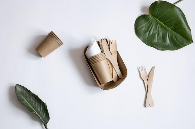 Ekologiczna jednorazowa zastawa stołowa wykonana z drewna bambusowego i papieru. kubki, noże i widelce na białym tle.