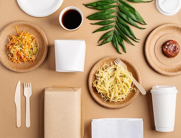 Ekologiczna jednorazowa zastawa stołowa z makaronem, sałatką i pączkiem leżała na brązowym tle. projekt makiety