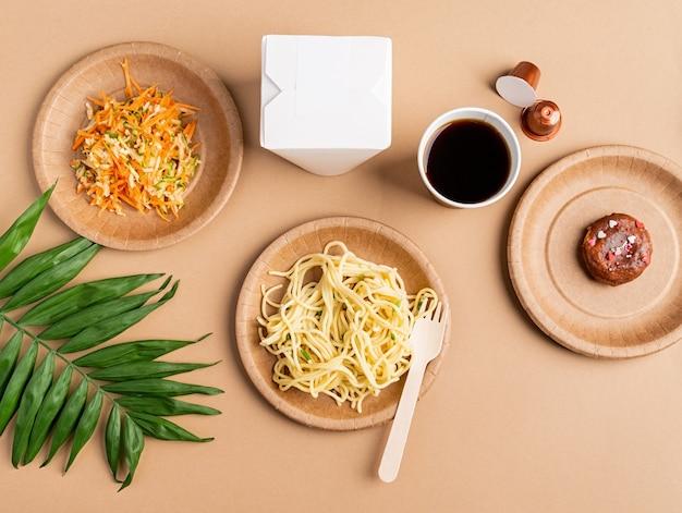 Ekologiczna jednorazowa zastawa stołowa zero waste z makaronem, sałatką i pączkiem, widok z góry płaski leżał na brązowym tle