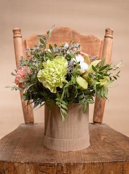 Ekologiczna kompozycja z bukietem kwiatów w kartonowym wazonie diy stojącym na starym drewnianym krześle na beżowym tle.