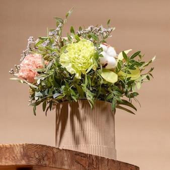 Ekologiczna kompozycja z bukietem kwiatów w kartonowym wazonie diy stojącym na starym drewnianym stole na beżowym tle z cieniami. nowoczesna świąteczna kartka okolicznościowa w stylu hygge.