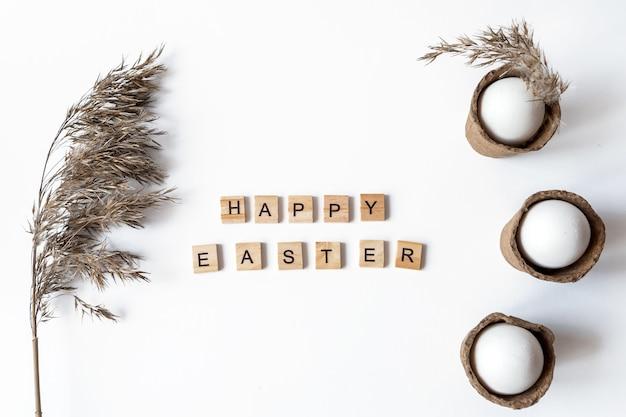 Ekologiczna koncepcja z białymi jajkami wielkanocnymi z trawą pampasową i napisem wesołych świąt.