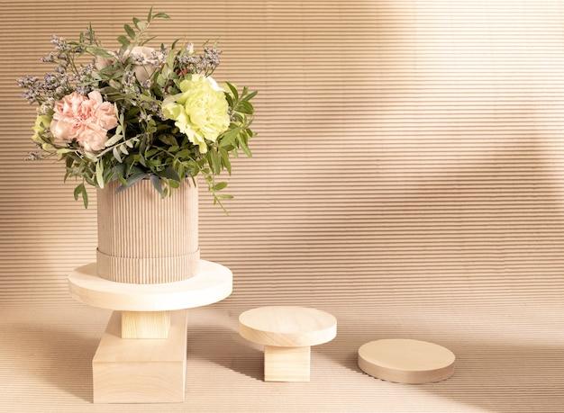 Ekologiczna minimalna monochromatyczna kompozycja z bukietem kwiatów i pustymi drewnianymi stojakami na produkty kosmetyczne na beżowym tekturowym tle z cieniami.