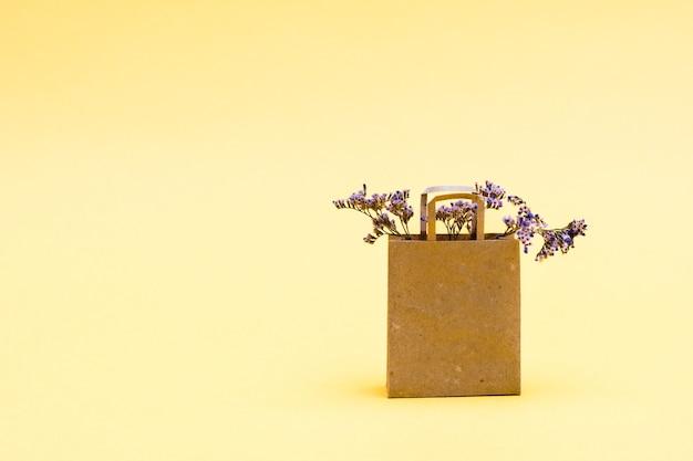 Ekologiczna papierowa torba na zakupy z suszonymi kwiatami na żółtym tle. sprzedaż prezentów w czarny piątek. skopiuj miejsce