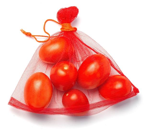 Ekologiczna siatka na zakupy warzyw. pomidory w siatce. pojedynczo na białym tle.