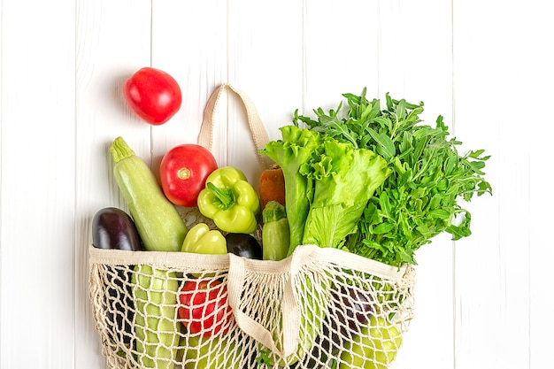 Ekologiczna siatkowa torba sklepowa z ekologicznymi zielonymi warzywami na białym drewnie
