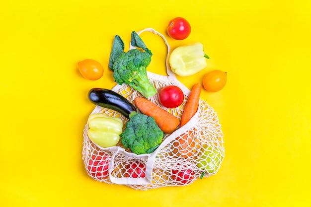 Ekologiczna siatkowa torba sklepowa z ekologicznymi zielonymi warzywami na żółto. leżał płasko, widok z góry.