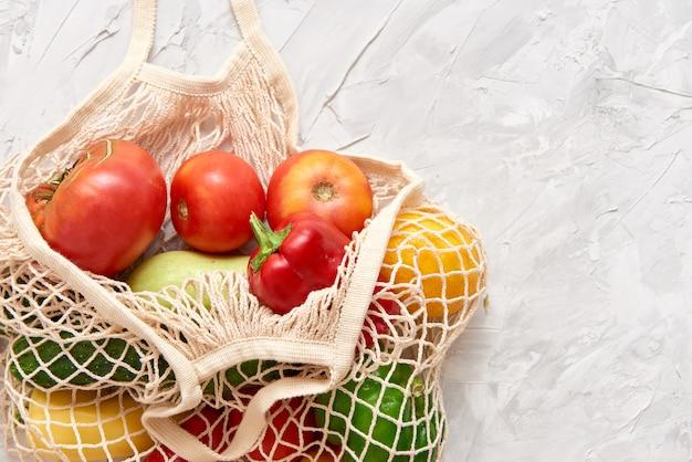 Ekologiczna siatkowa torba z owocami i warzywami.