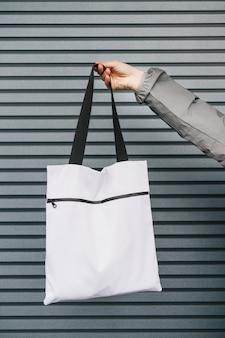 Ekologiczna torba na zakupy wielokrotnego użytku z zamkiem w ludzkich rękach.