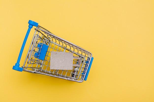 Ekologiczna torba papierowa rzemieślnicza w metalowym koszyku na żółtym tle. czarny piątek, sprzedaż prezentów. widok z góry