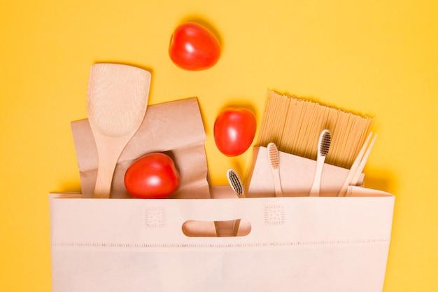 Ekologiczna torba z tkaniny z produktami na żółtym tle, jedzeniem, drewnianymi sprzętami kuchennymi i bambusowymi szczoteczkami do zębów widok z góry