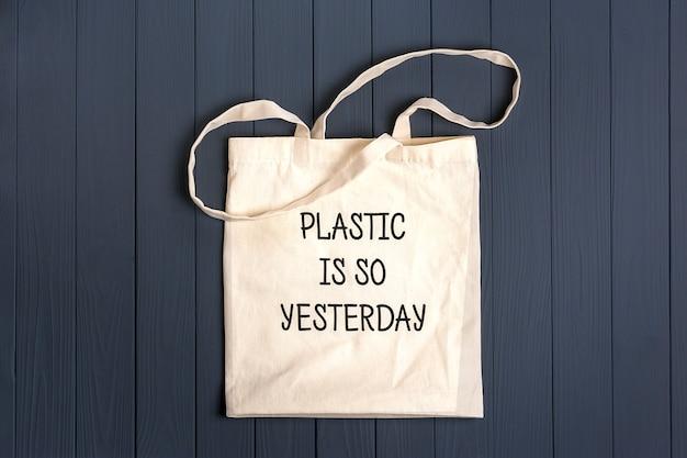 Ekologiczna torba z włókniny na ciemnoszarym drewnianym stole plastik jest wczoraj