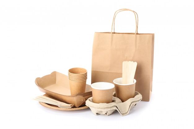 Ekologiczna zastawa stołowa i papierowa torba odizolowywający na bielu. naczynia jednorazowe