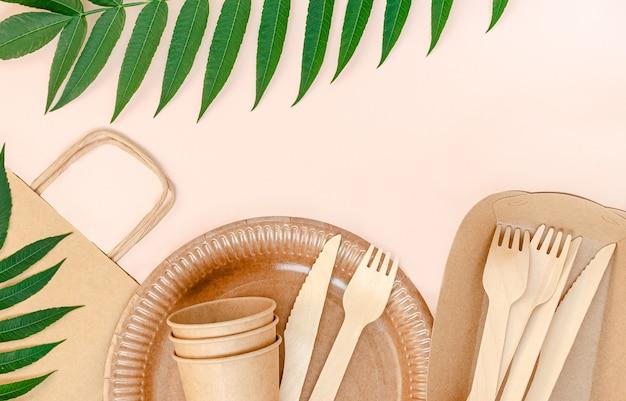 Ekologiczna zastawa stołowa na piknik na różowym tle.