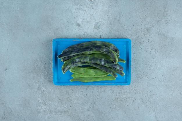 Ekologiczna zielona fasola na niebieskim talerzu.