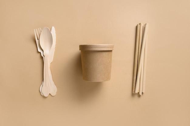 Ekologiczne, biodegradowalne jednorazowe kubki i pojedyncze łyżeczki, widelce, bambusowe słomki na beżowej przestrzeni
