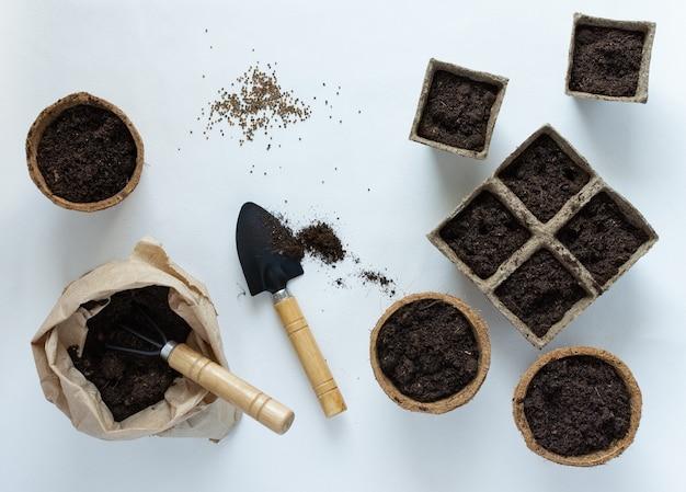 Ekologiczne doniczki do sadzonek i nasion na białym tle, mały worek z kielnią do ziemi i ogrodu oraz grabiami