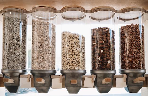 Ekologiczne dozowniki sklepowe zero waste na ziarna orzechów w ekologicznym sklepie spożywczym bez plastiku