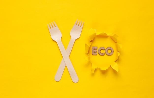Ekologiczne drewniane widelce na żółtym tle. słowo eko na papierze z rozdartym otworem. minimalizm.