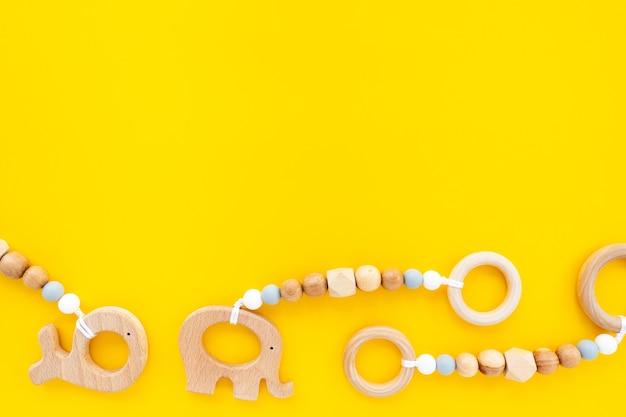 Ekologiczne drewniane zabawki dla dzieci na jasnożółtym tle, widok z góry, płaski układ, miejsce na tekst. płaska kompozycja, tło dla dzieci.