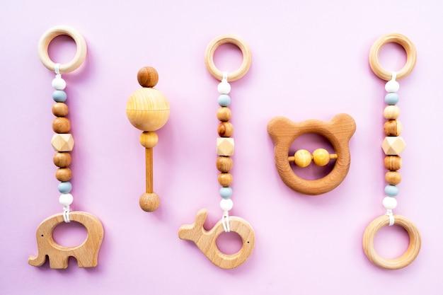 Ekologiczne drewniane zabawki dla dzieci na różowym tle, widok z góry, układ płaski, miejsce do kopiowania. płaska kompozycja, tło dla dzieci.