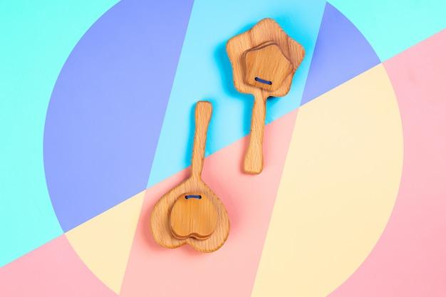Ekologiczne drewniane zabawki, grzechotki w kształcie serca, gwiazdy na różowym, niebieskim i żółtym tle na białym tle.