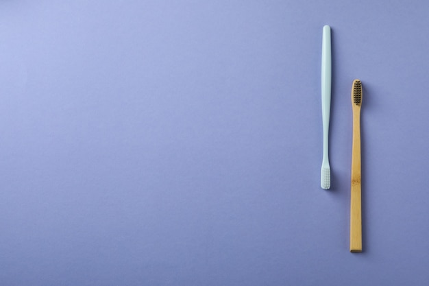 Ekologiczne i plastikowe szczoteczki do zębów na fioletowym tle
