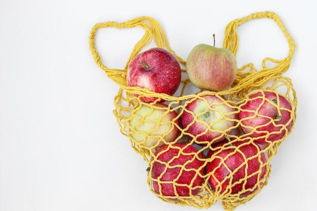 Ekologiczne jabłka w żółtej tekstylnej torbie na zakupy na białym tle, orientacja pozioma, koncepcja zero waste