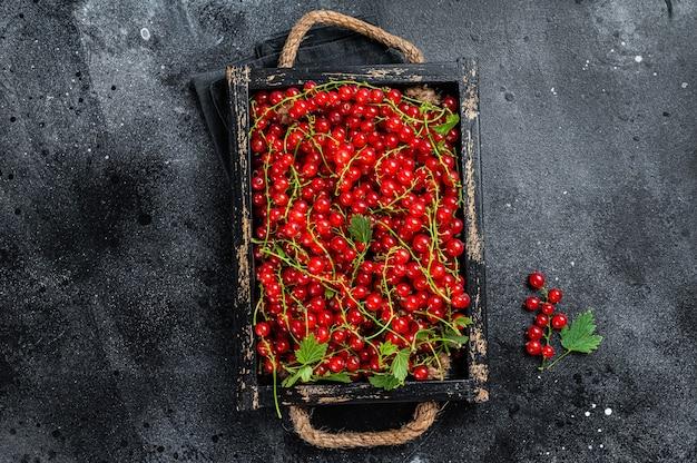 Ekologiczne jagody czerwonej porzeczki w drewnianym pudełku. czarne tło. widok z góry.