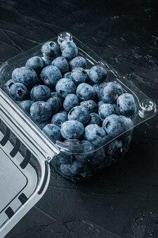 Ekologiczne jagody w plastikowym pudełku, na czarnym tle