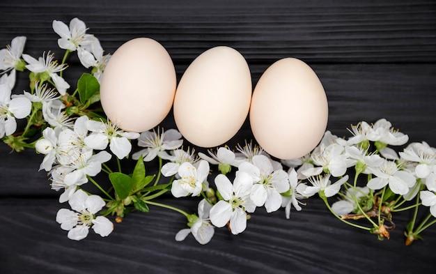Ekologiczne jaja kurze, produkty ekologiczne. skład kwitnących gałęzi drzew. naturalne pisanki z białymi wiosennymi kwiatami na ciemnym drewnianym stole. koncepcja wesołych świąt.