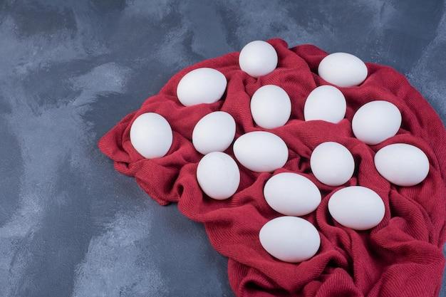 Ekologiczne jajka na kawałku ręcznika kuchennego.
