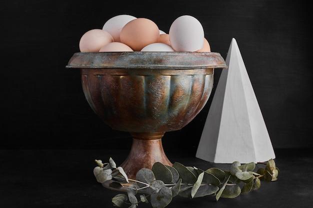 Ekologiczne jajka w metalowej filiżance.