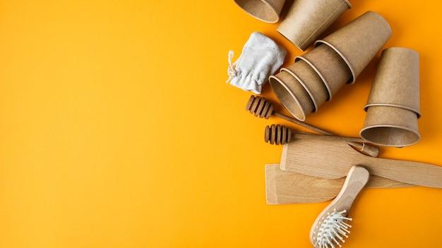 Ekologiczne jednorazowe kubki papierowe, drewniane przybory kuchenne, szczotka do włosów i bawełniana torba