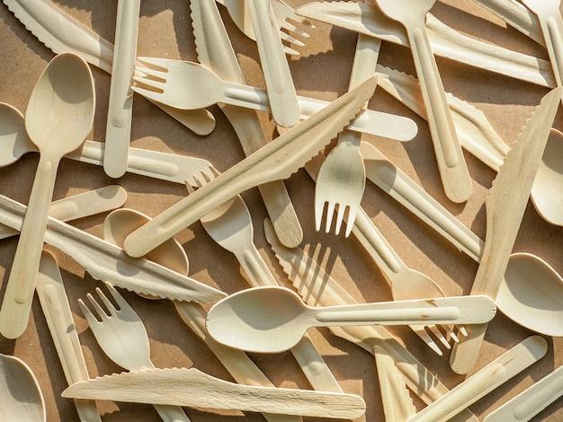 Ekologiczne jednorazowe naczynia kuchenne na tle papieru rzemieślniczego. drewniane widelce, noże i łyżki. ekologia, koncepcja zero odpadów. widok z góry. leżał płasko.