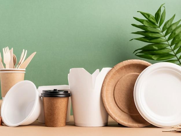 Ekologiczne jednorazowe przybory ekologiczne. talerze, kubki, miska, widelce i pudełko wok na zielonym tle