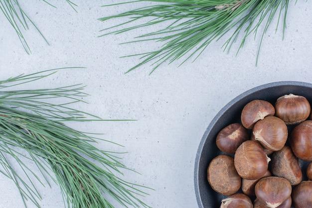 Ekologiczne kasztany na czarnej patelni z gałęziami.