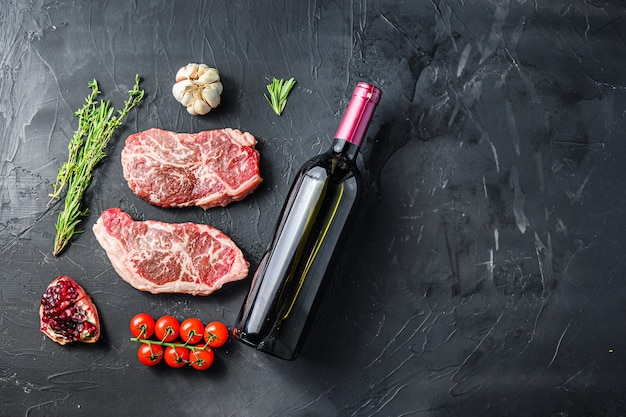 Ekologiczne kawałki steków z górnym ostrzem, z butelką czerwonego wina i kieliszkami, ziołami i przyprawami