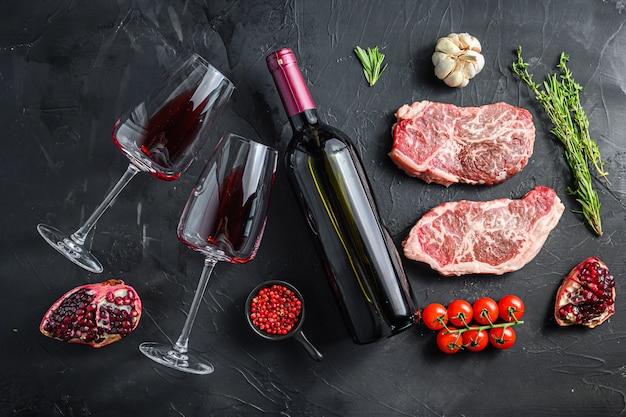 Ekologiczne kawałki steków z górnym ostrzem, z butelką czerwonego wina i kieliszkami