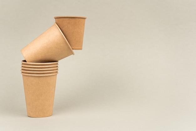 Ekologiczne kieliszki na wynos na beżowym tle kubki papierowe rzemieślnicze